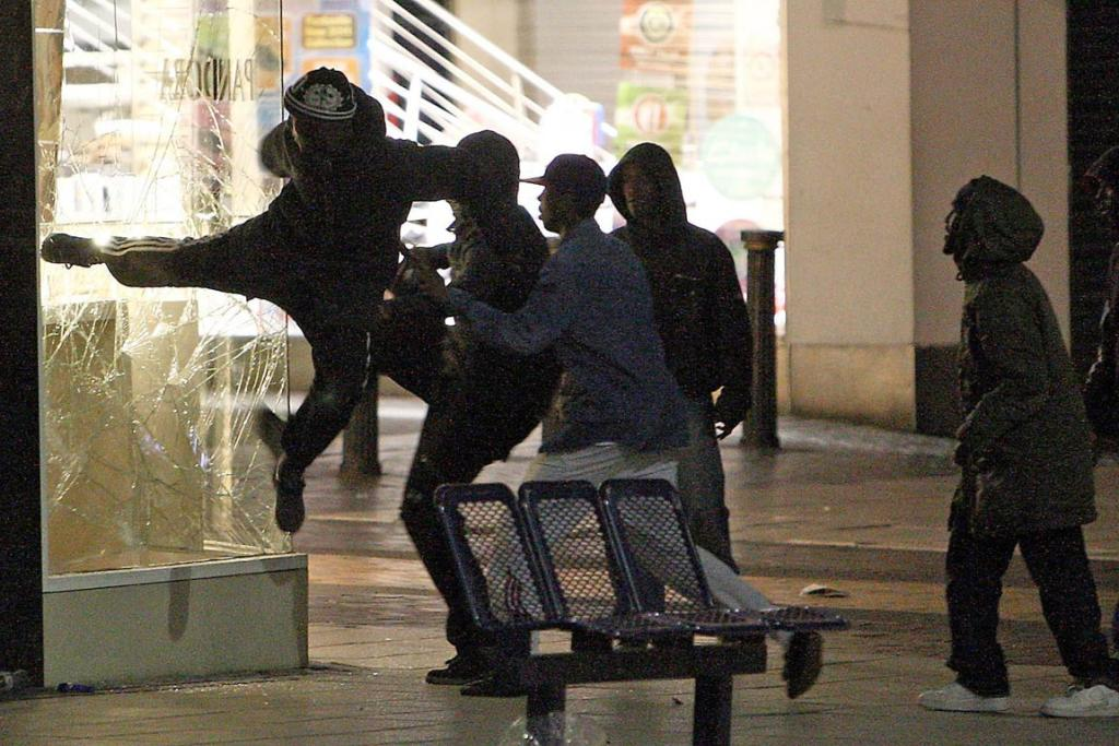 People try to kick in the window of a jeweller's shop near the Bullring shopping centre in Birmingham as violence spread outside London.