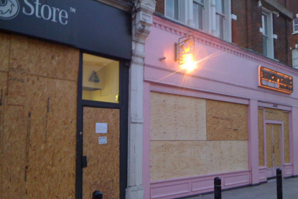 The day after the riots and the shops outside Alex Spence's London flat are boarded up.