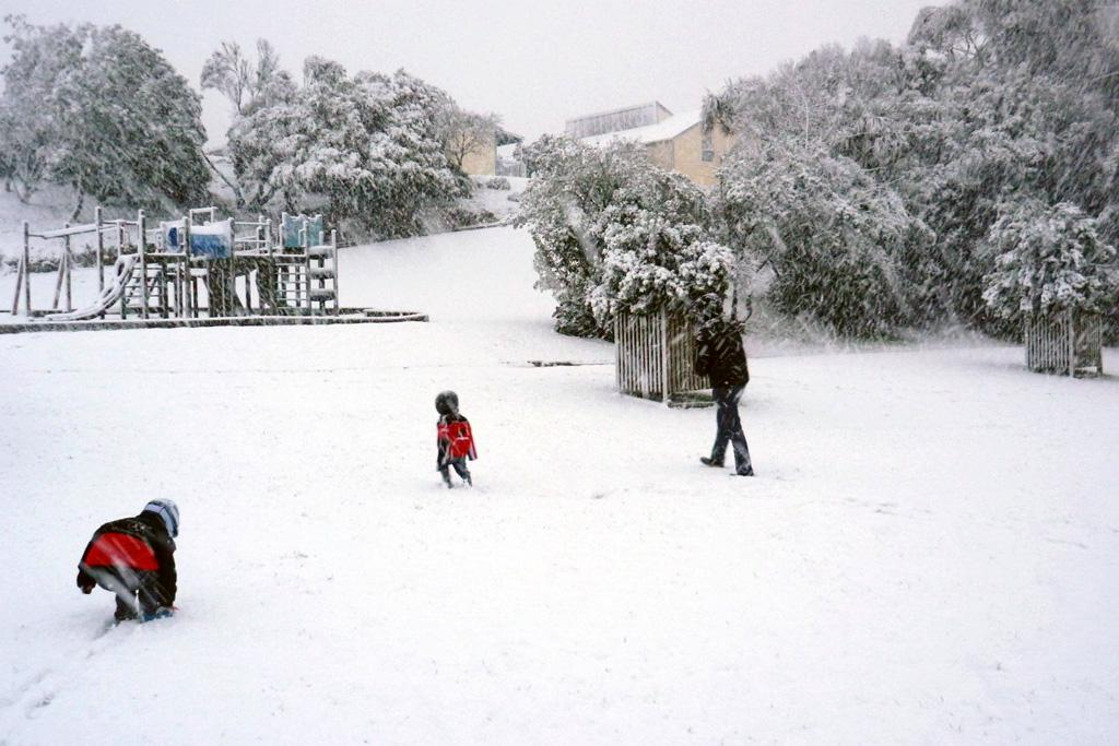 A family plays in the snow at Westpark School on Sunday.