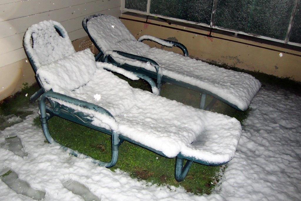 Deck chairs covered with snow at Titahi Bay.