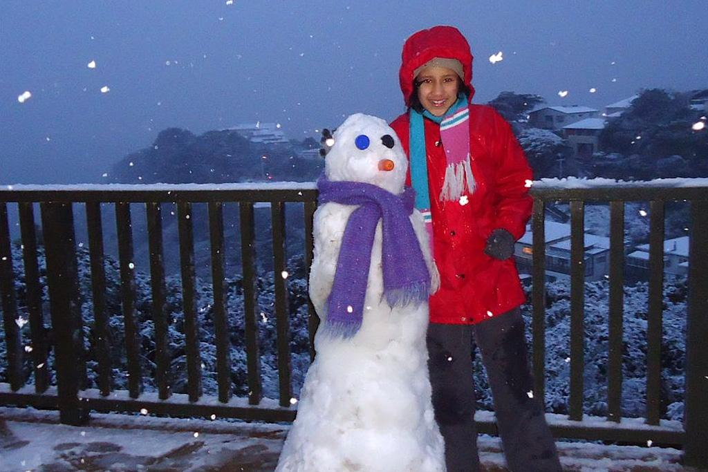 Anjali Gupta with a snow man she made on Ashton Fitchett Dr in Brooklyn.