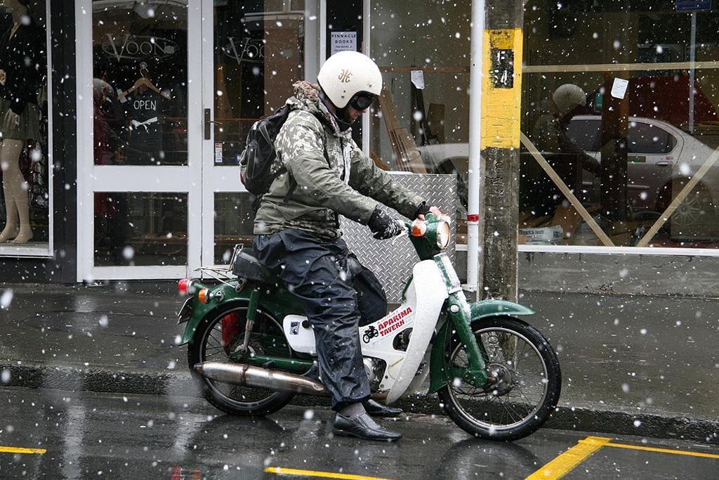A motorcyclist rides down Willis St during snow fall on Monday.
