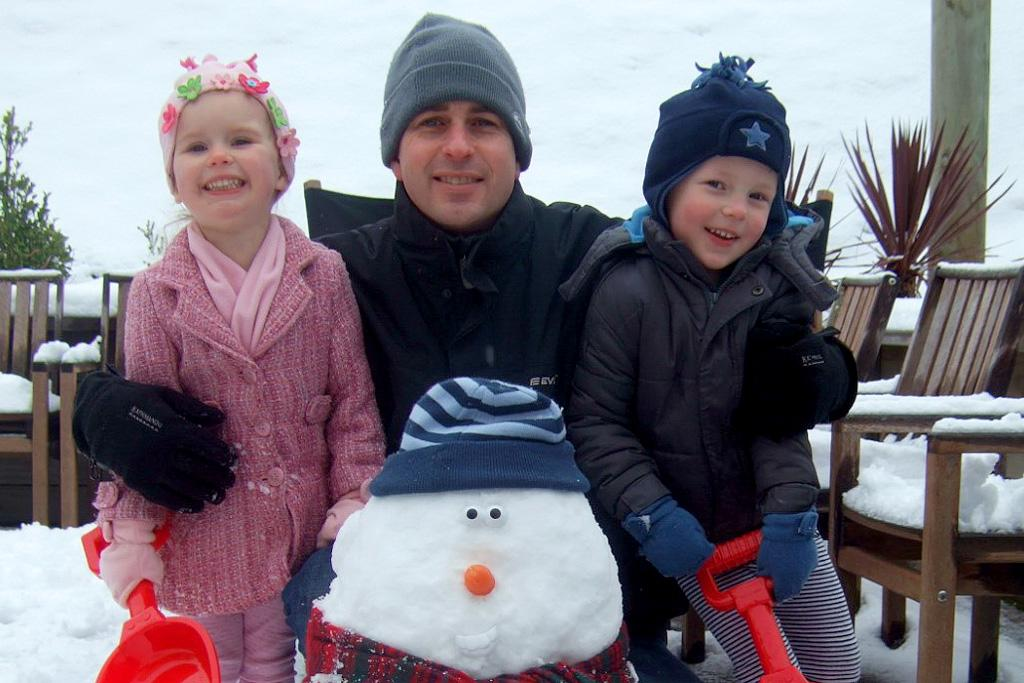 The McKenna family - Yasmyn, 3, Grant, and Kaeden, 4 - pose with their snowman in Broadmeadows on Monday.