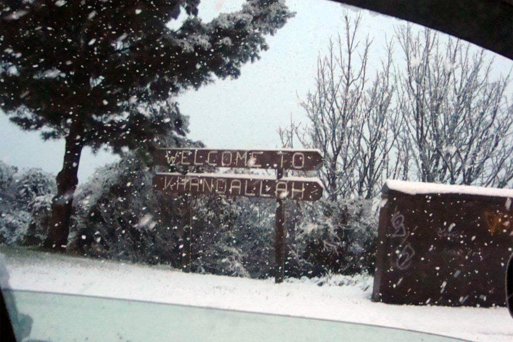 The Welcome To Khandallah sign is blanketed in snow on Monday.