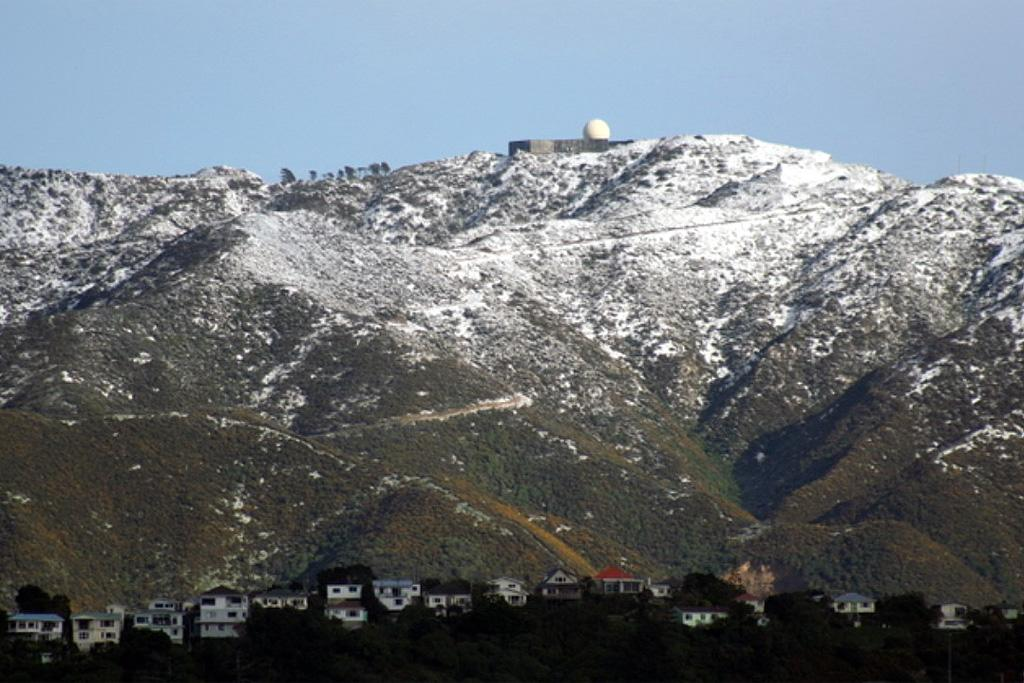 Snow can be seen on hills behind Highbury after heavy snow fell in Wellington.