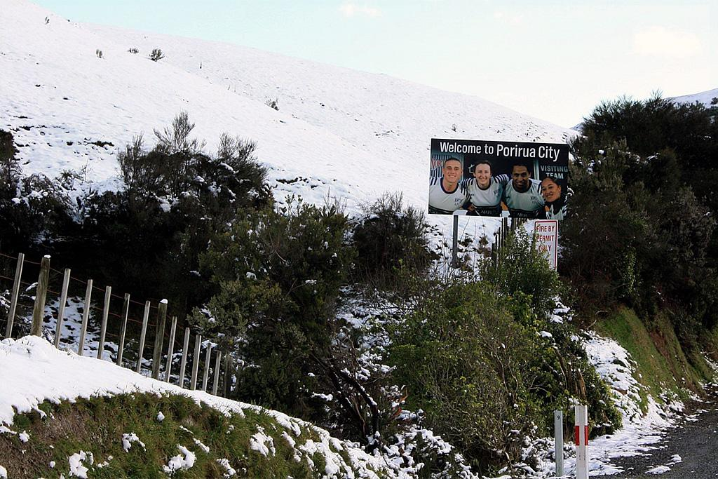 A sign at the edge of Porirua surrounded by snow-covered fields.