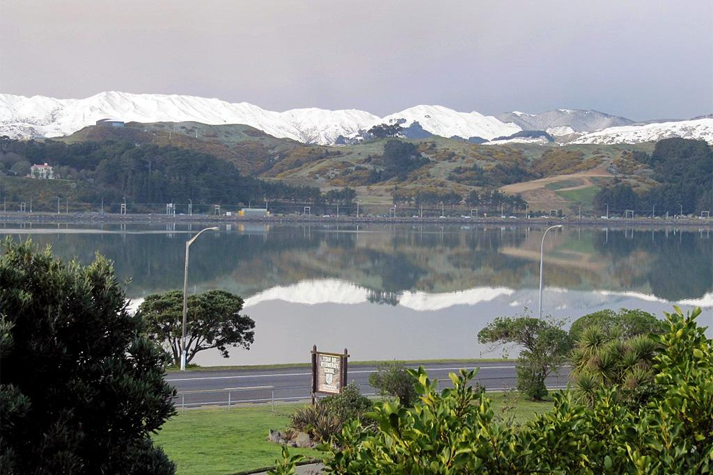 Porirua harbour with snow-covered hills above the motorway.