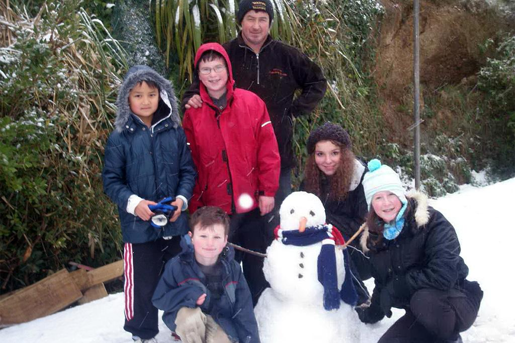 The Ryan family with their first-ever snowman which they built in Grenada Village.