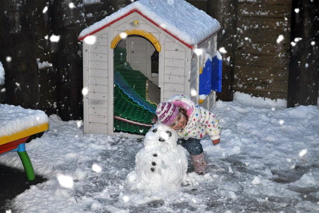 Sofia Walker, 3, poses with her snowman at Mauldeth Terrace, Churton Park.