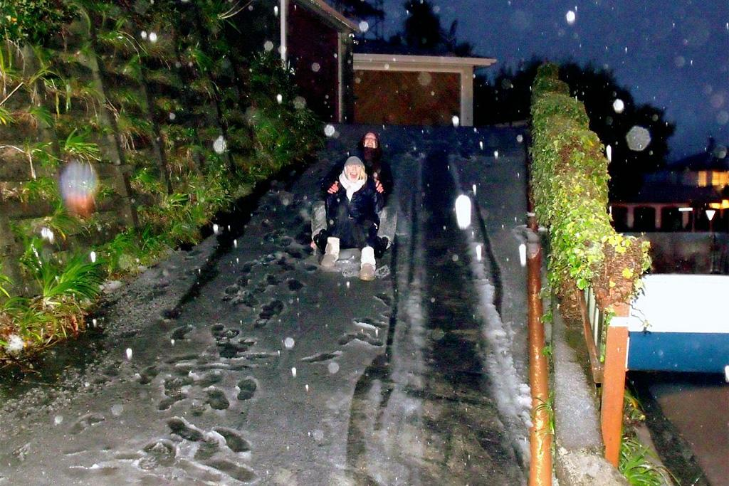 Zephyr Harriet and Madison Millar slide down a driveway to make the most of the slick surface.