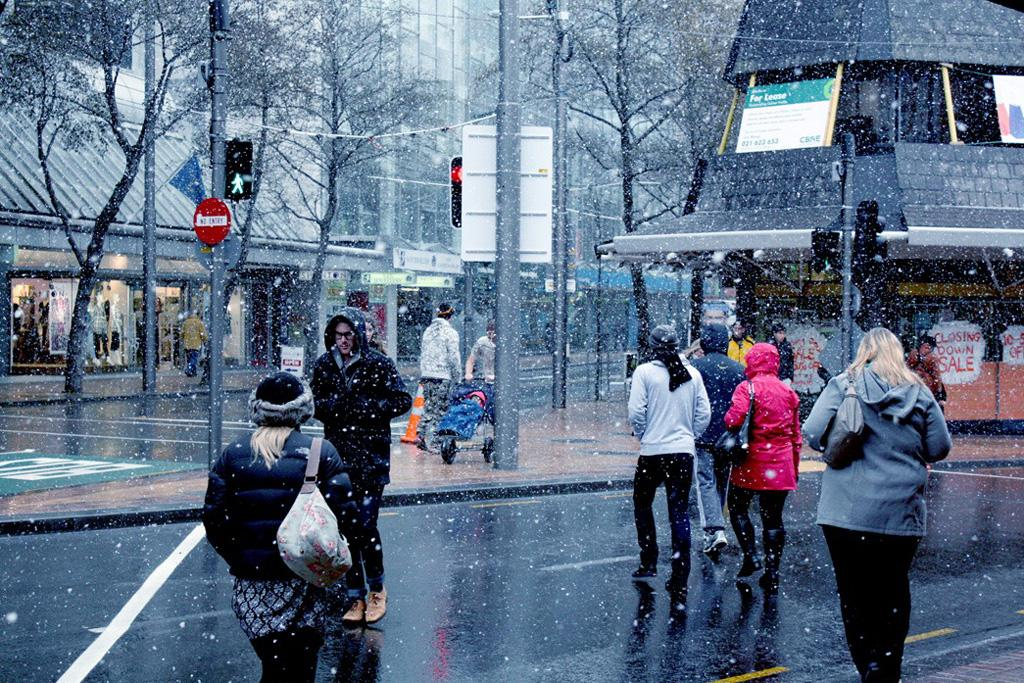 Pedestrians shelter from the falling snow in central Wellington.