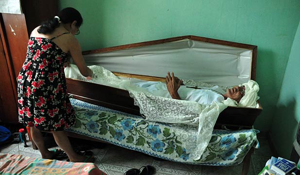 Zeli Ferreira Rosse and his wife Cleusa Pereira Rosse, re-enact how Rosse sleeps in a coffin in Minas Gerais, Brazil.