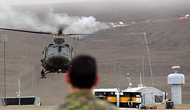 A member of the Canadian Forces watches a helicopter in front of the wreckage of a plane that crashed in the hills behind, in Resolute Bay, Nunavut.