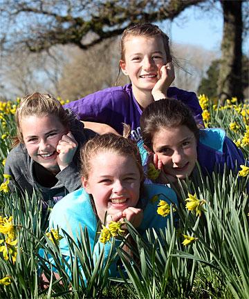 SPRINGING UP: Egmont Village School pupils Chelsea Tyler, left, Georgia Dey, Summer Wilkins and Brianna Keightley-Trigg, all 12, are all smiles as they lie among the new season's daffodil blooms.
