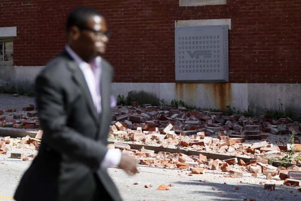 A man walks past bricks that fell off of a house after an earthquake was felt in Baltimore.