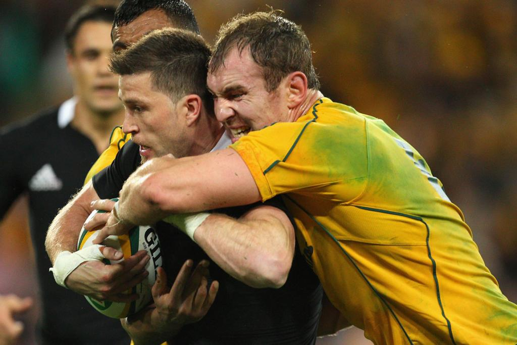 All Blacks winger Cory Jane is wrapped up by Wallabies flanker Rocky Elsom.