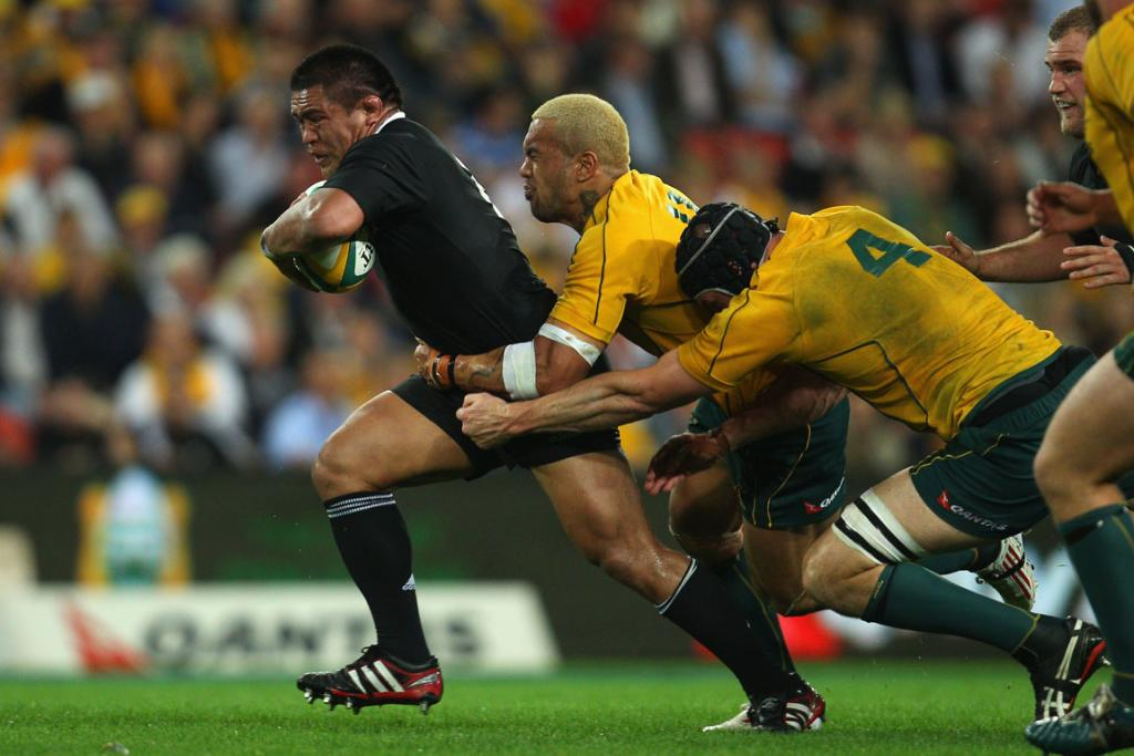 All Blacks hooker Keven Mealamu powers through the tackle of Wallabies winger Digby Ioane.