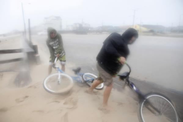 Two unidentified boys get back on their bikes as they leave the beach while being blasted with sand and rain from strong winds on the Outer Banks in Kill Devil Hills as Hurricane Irene reaches the North Carolina coast.