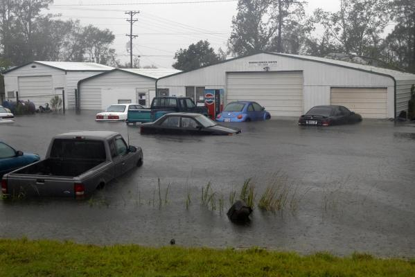 Vehicles sit in flood waters at a auto repair shop as Hurricane Irene hits the North Carolina coast of the US.