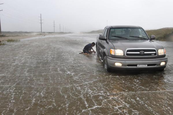 Ron Briethaup, 48, of Buxton, North Carolina, works to free his fiancee's truck after it got stuck on a flooded section of highway as Hurricane Irene lashed the eastern coast of the US.