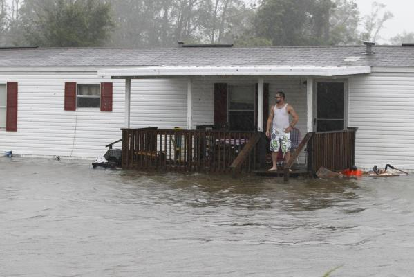 Jarod Wilton looks at the flood waters rising to his doorstep in Alliance, North Carolina, as Hurricane Irene hits the US.