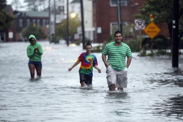 People wade through a street flooded by Hurricane Irene in Manteo, North Carolina, US.