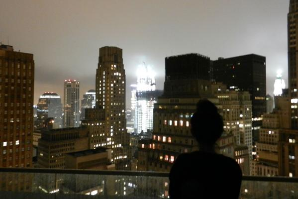 New Zealander Joyce Santiago watches the New York skyline for Hurricane Irene's approach from the roof deck of her apartment.