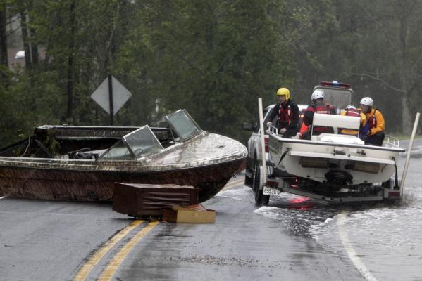 The Arr-Mac water rescue team from Wayne County manoeuvres around a beached boat in the middle of Highway 304 in Mesic, North Carolina.