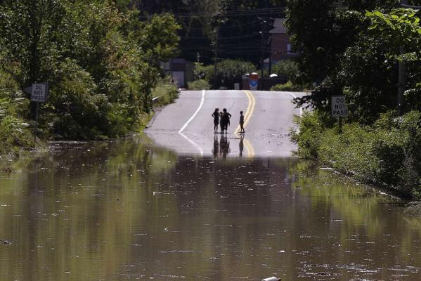 Children stand on the far side of a flooded portion of Massachusetts Route 5 which is closed to traffic in Northhampton due to flooding from tropical storm Irene.