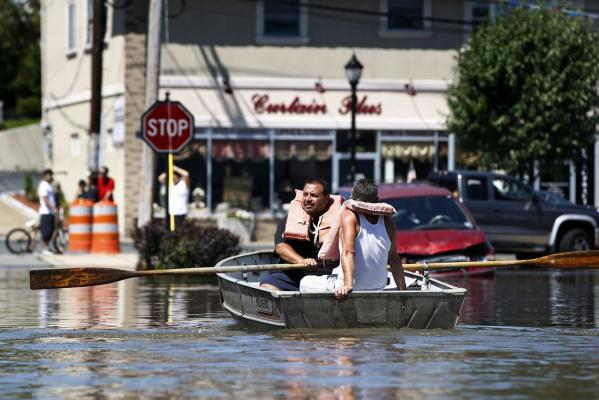Residents use a boat to examine flooding in the town of Totowa, New Jersey.