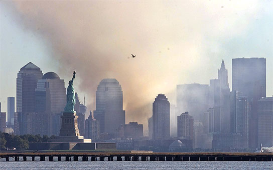Smoke from the remains of New York's World Trade Center shrouds lower Manhattan as the Statue of Liberty stands in the foreground and a lone seagull flies by in this image taken across New York Harbour.