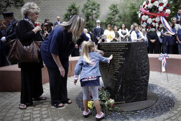 The family of Captain David T. Wooley, including his widow Linda (L), daughter Stacey (C) and granddaughter (R), touch the commemoratory stone and leave flowers during a memorial service for the firehouse of Engine 54, Ladder 4 and Battalion 9, marking the 10th anniversary of the 9/11 attacks on the World Trade Center.