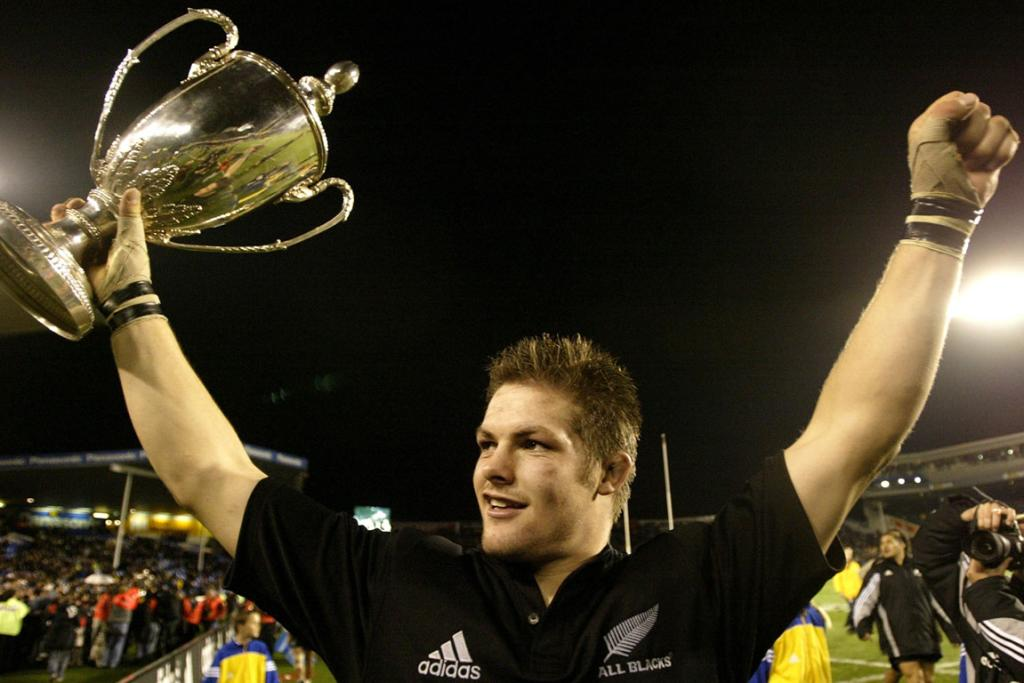 Richie McCaw celebrates with the Tri-Nations trophy after the second Bledisloe Cup match in 2003.