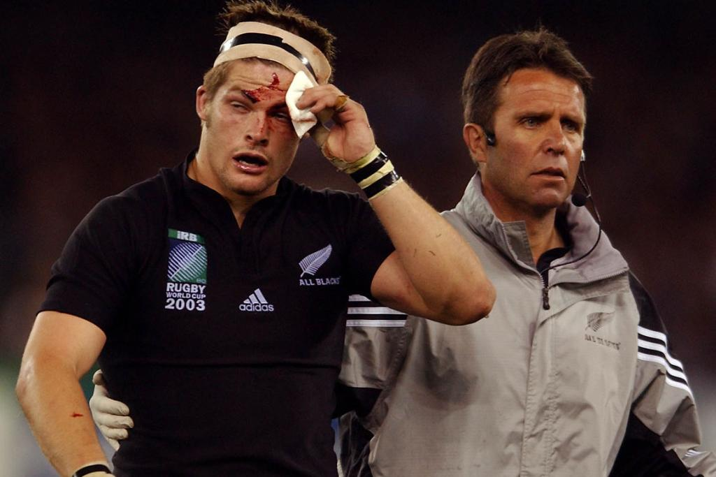 Richie McCaw is escorted from the field to the blood bin for the second time during the All Blacks' 29-9 win over South Africa in the quarterfinal of the Rugby World Cup in 2003.