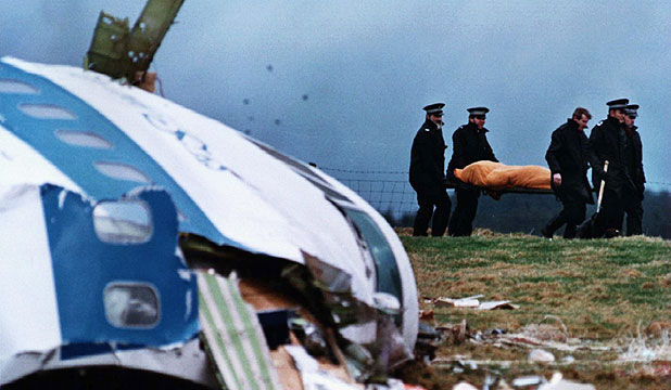 Rescue personnel carrying a body away from the site of the 1988 Lockerbie airplane bombing in Scotland.