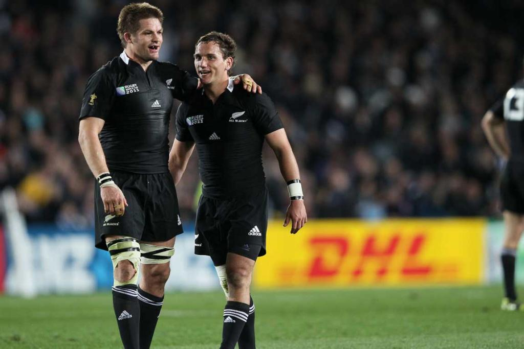 All Black captain Richie McCaw encourages All Black replacement Aaron Cruden.