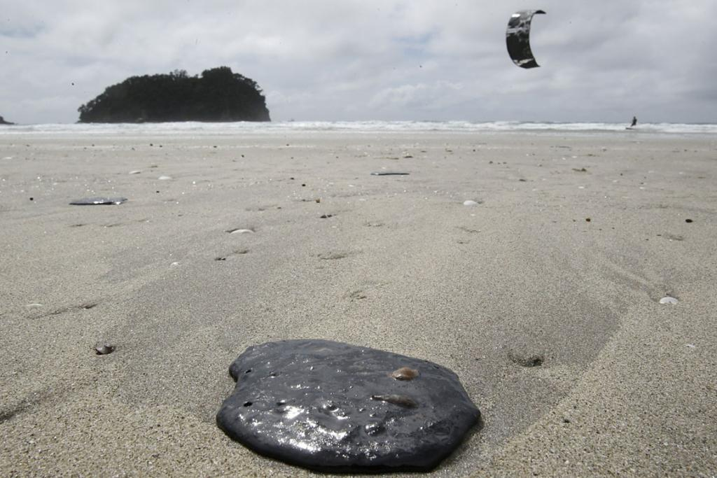 DIRTY MESS: Mt Manganui beach is awash with blobs of oil from the stricken ship Rena.
