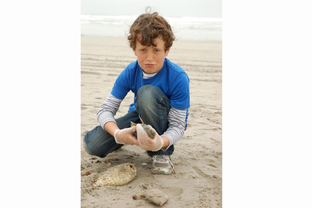 Sunny, 9 years, with his dead fish on Mt Maunganui beach.