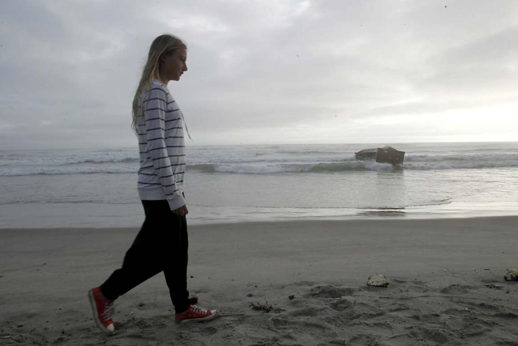 A woman walks past a container from the stricken Rena, washed up on Mt Maunganui Beach, Thursday October 13.