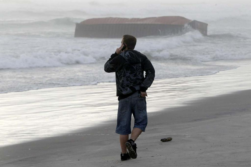 A man walks on Mt Maunganui Beach, with a container from the stricken Rena in the distance, Thursday October 13.