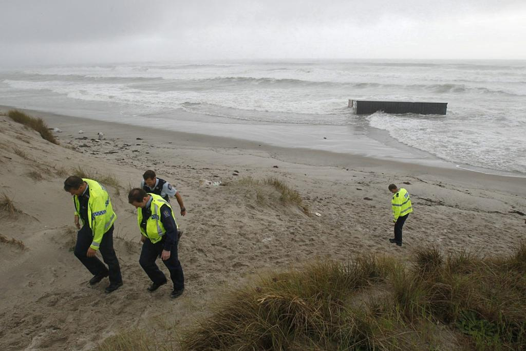 Police check a container that has washed up on Mt Maunganui beach.