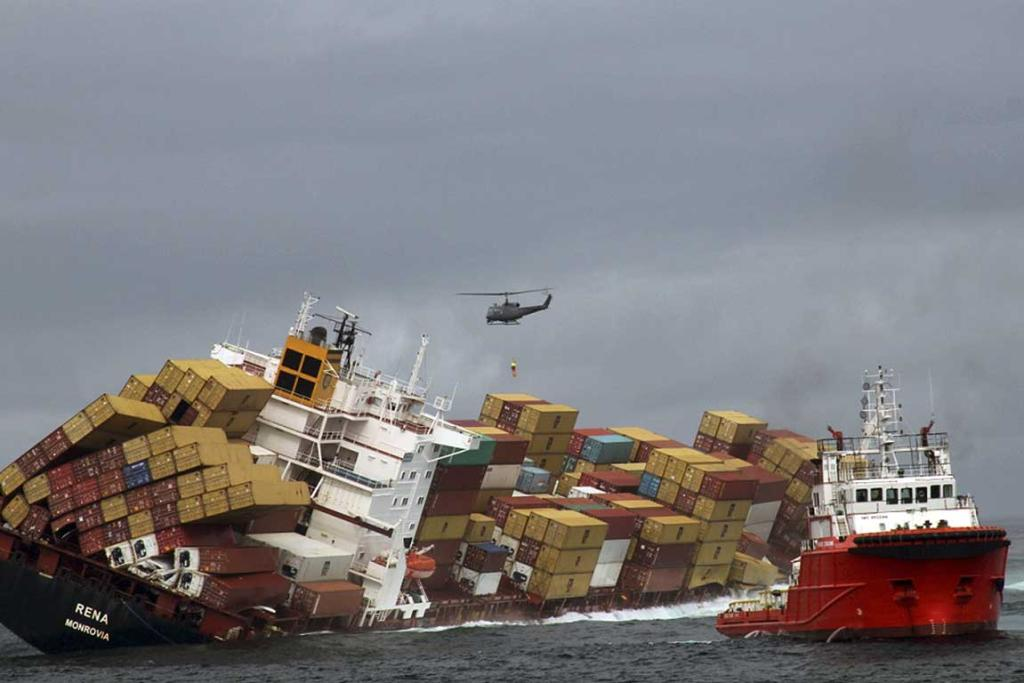A Royal New Zealand Air Force helicopter winches a salvage expert onto the stricken container ship Rena.