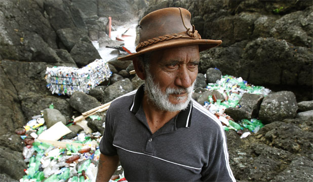 RUBBISH DUMP: Motiti Island kaumatua Graham Hoete surveys the bay where bundled plastic waste has washed ashore.