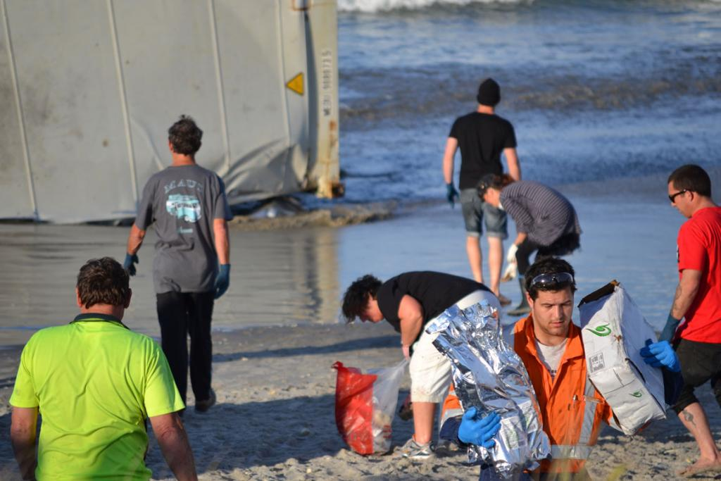 Volunteers clean up packets of burger patties from the broken container washed up on Mount Maunganui Beach.