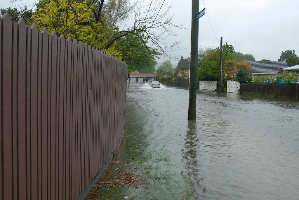 WATERY DRIVE: A car drives through a water-covered Gainsborough St, Hoon Hay, in Christchurch.
