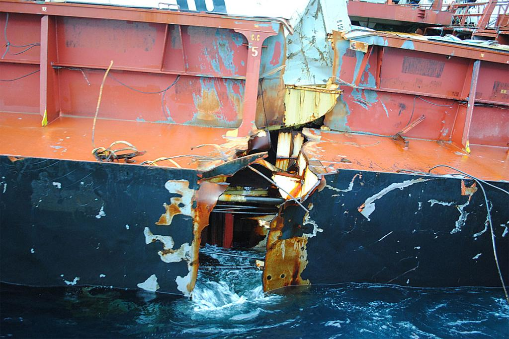 The ocean washes in and out of the wide fracture on Rena's starboard side.