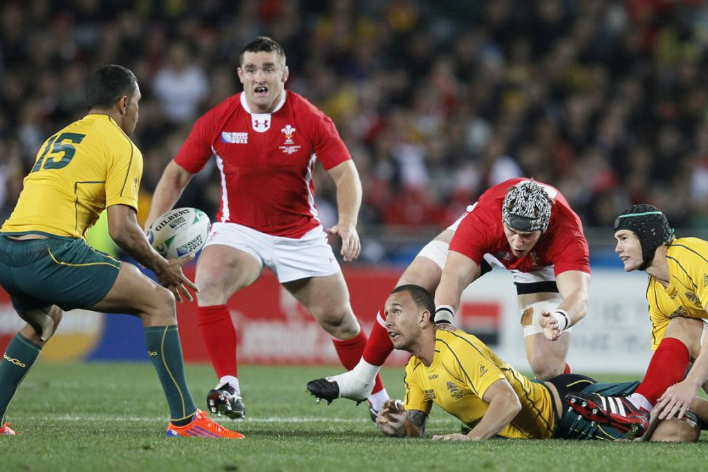 Flyhalf Quade Cooper of the Wallabies looks to offload as he is wrapped up by the Welsh defence.