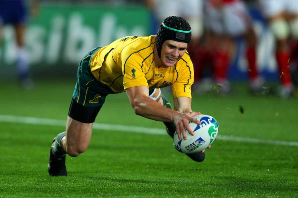 Centre Berrick Barnes of the Wallabies dives over to score the opening try.
