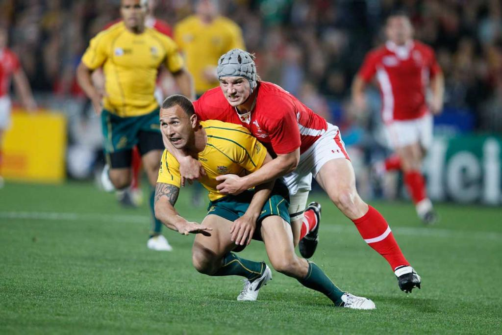 Australia first-five Quade Cooper is tackled by Wales blindside flanker Danny Lydiate.