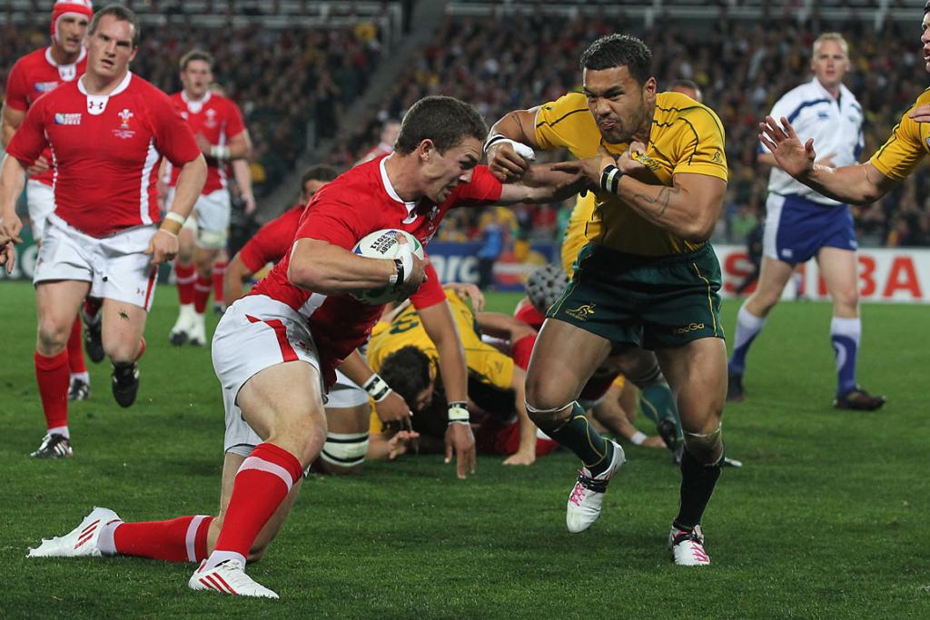 Wales right wing George North fends Australia left wing Digby Ioane.